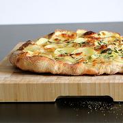 Kartoffelpizza på skærebræt